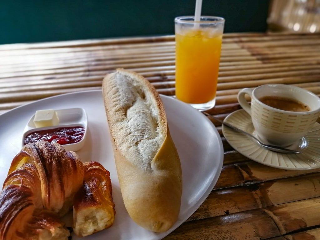 Petit-déjeuner à la boulangerie-pâtisserie de Samui avec croissant, café, baguette, beurre, confiture et jus d'orange.