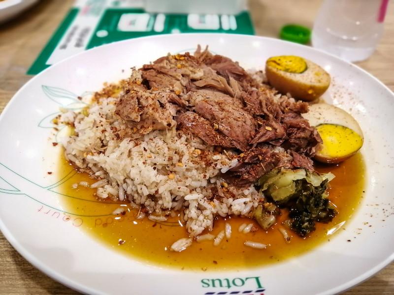 Assiette de Khao Kha Mu, viande de porc avec riz, œuf et laitue marinée.